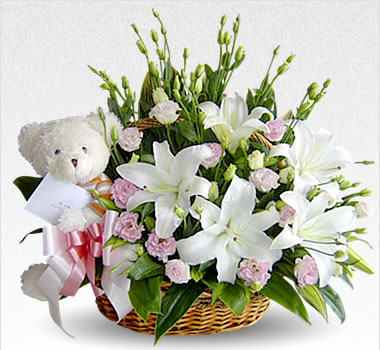 Lilies and teddy bear in a basket